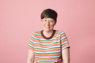 Megan Nairn, League of Geeks' Studio Manager, smiles in front of a pink background